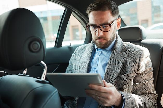 Ernster bärtiger geschäftsmann in brillen, die auf rücksitz im auto sitzen und digitales tablett verwenden
