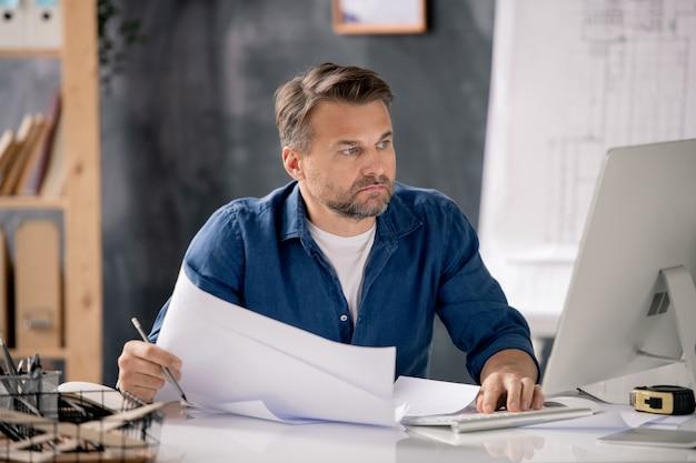 Ernster bärtiger ingenieur mit papieren, die computerbildschirm betrachten, während sie am schreibtisch vor dem monitor im büro sitzen