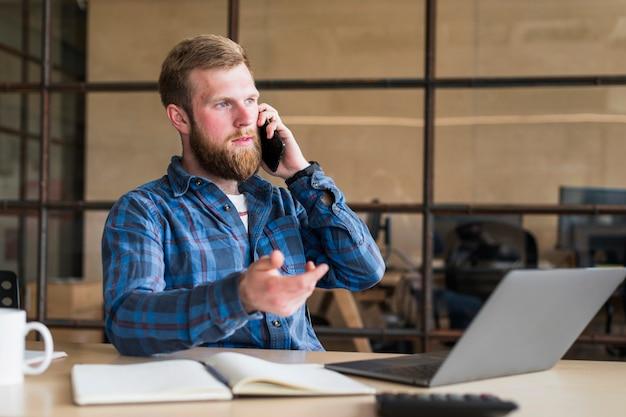 Ernster bärtiger mann, der auf mobiltelefon am arbeitsplatz spricht
