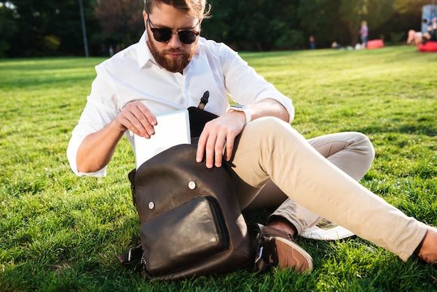 Ernster bärtiger mann, der draußen auf gras sitzt und tablet-computer von seinem rucksack erhält
