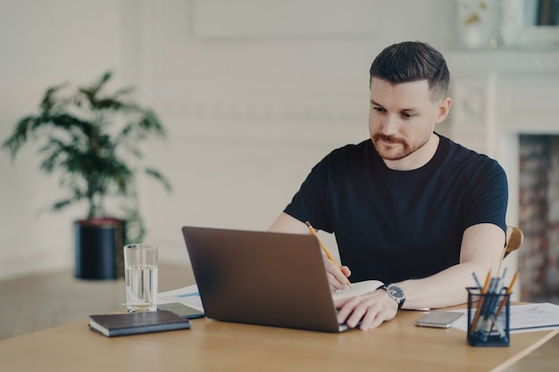 Ernster bärtiger mann schreibt informative notizen, während er webinar auf laptop-computern sieht, die aus der ferne in lässigen t-shirt-posen am arbeitsplatz gegen das innenministerium arbeiten. moderner arbeitsplatz