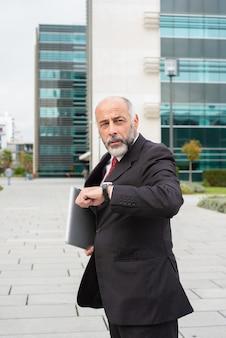 Ernster beschäftigter reifer geschäftsmannlaptop auf seinem weg zum büro