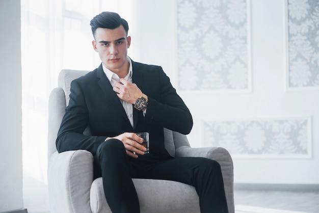 Ernster blick. junger eleganter kerl im schwarzen anzug sitzt auf weißem stuhl und hält glas mit alkohol.