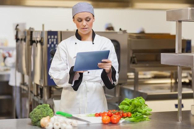 Ernster chef, der digitale tablette neben dem gemüse verwendet