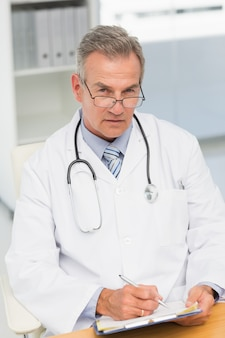 Ernster doktor, der an seinem schreibtischschreiben auf klemmbrett sitzt