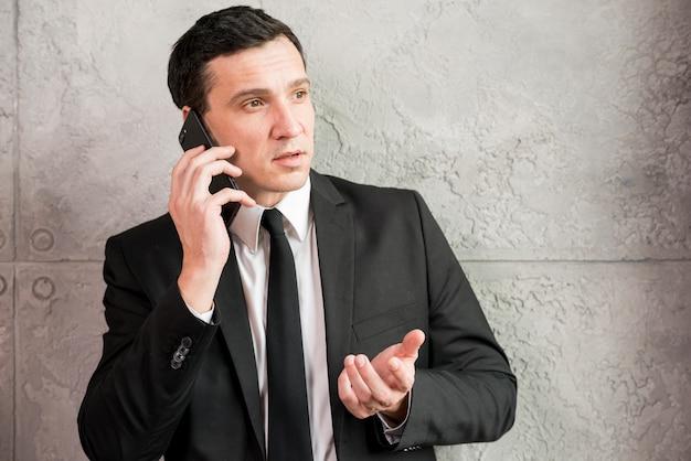 Ernster erwachsener geschäftsmann, der am telefon spricht