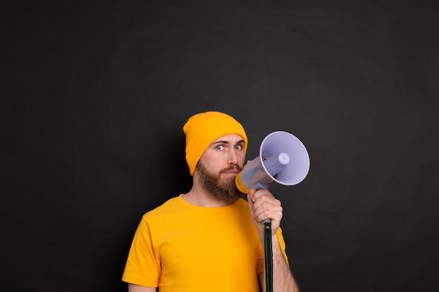 Ernster europäischer mann mit megaphon auf schwarzem hintergrund