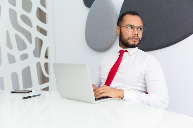 Ernster fachmann, der an computer arbeitet
