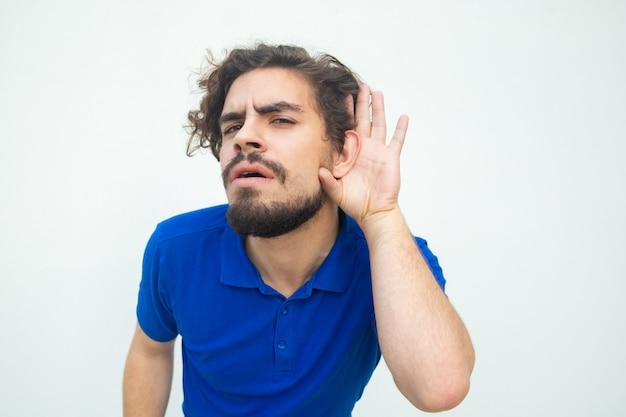 Ernster fokussierter kerl, der auf geheimnis hört