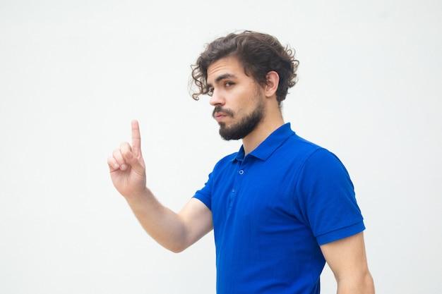 Ernster fokussierter kerl, der zeigefinger zeigt