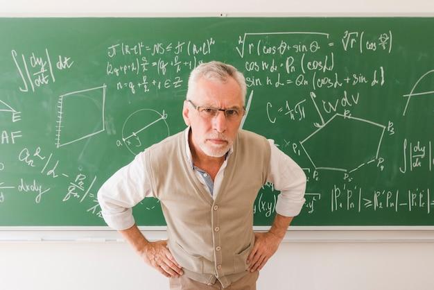 Ernster gealterter professor im hörsaal, der kamera betrachtet