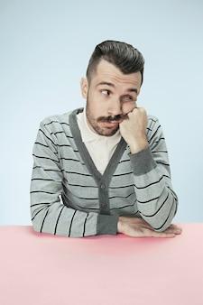 Ernster, gelangweilter und langweiliger geschäftsmann, der am tisch auf blauem studiohintergrund sitzt. das porträt im minimalismusstil