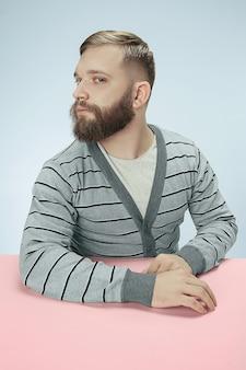 Ernster geschäftsmann, der am tisch auf blauem studiohintergrund sitzt. das porträt im minimalismusstil