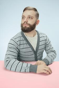 Ernster geschäftsmann, der am tisch auf blauem studiohintergrund sitzt.