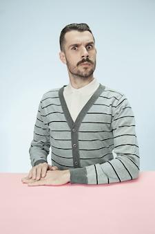 Ernster geschäftsmann, der am tisch sitzt das porträt im minimalismusstil