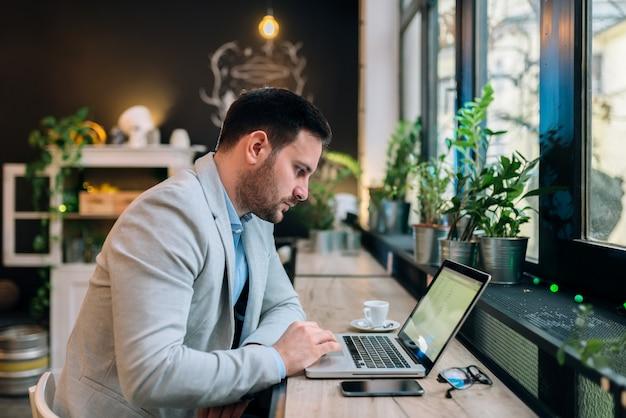 Ernster geschäftsmann, der an einem laptop am café arbeitet.