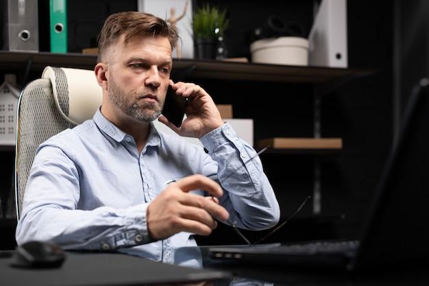 Ernster geschäftsmann, der an einem laptop arbeitet und an einem handy spricht