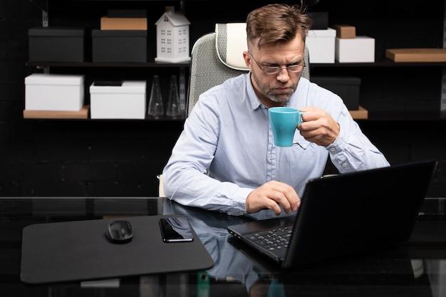 Ernster geschäftsmann, der an laptop arbeitet und kaffee trinkt