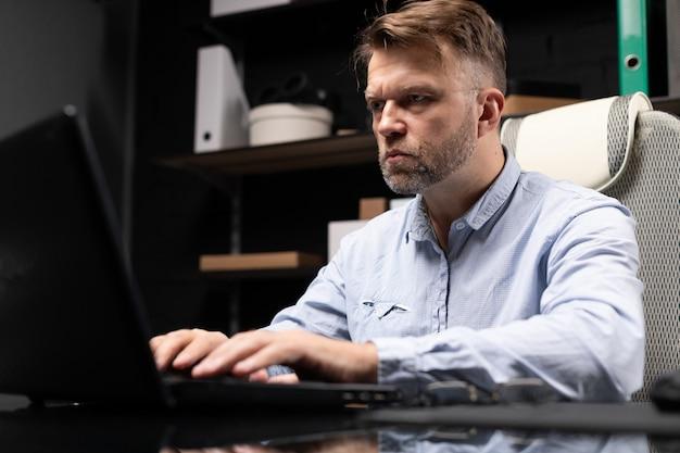 Ernster geschäftsmann, der auf laptop im stilvollen, modernen büro schreibt