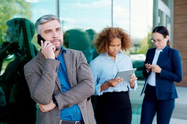 Ernster geschäftsmann, der auf smartphone spricht, während durch bürogebäude auf hintergrund der jungen frauen, die gadgets verwenden