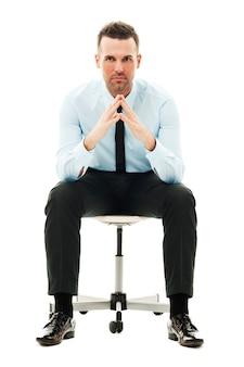 Ernster geschäftsmann, der auf stuhl sitzt