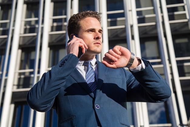 Ernster geschäftsmann, der die zeit spricht am telefon überprüft.