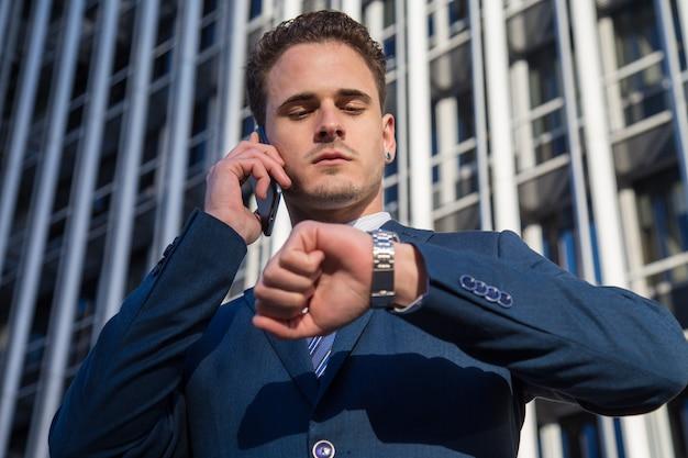 Ernster geschäftsmann, der die zeit spricht am telefon überprüft