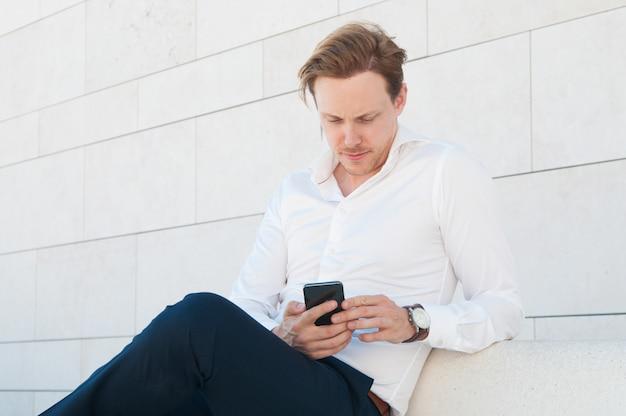 Ernster geschäftsmann, der draußen smartphone auf bank verwendet