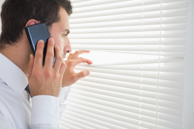 Ernster geschäftsmann, der durch rollbahn beim anrufen ausspioniert