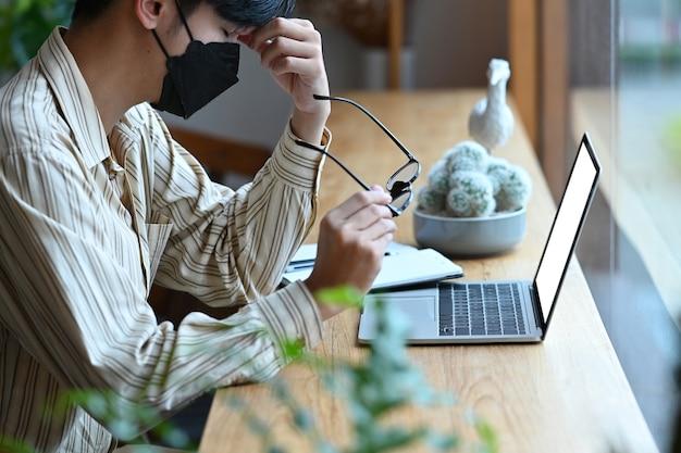 Ernster geschäftsmann, der eine brille hält und mit laptop-computer arbeitet.