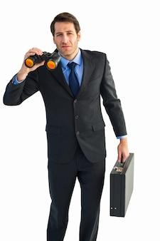 Ernster geschäftsmann, der ferngläser und einen aktenkoffer hält Premium Fotos