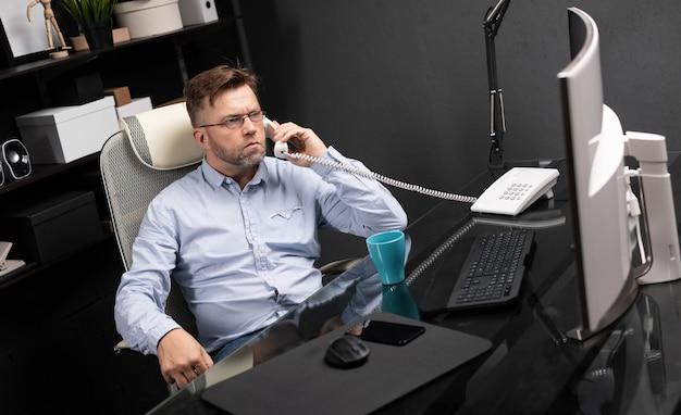 Ernster geschäftsmann, der im büro am computertisch arbeitet und auf überlandleitung spricht