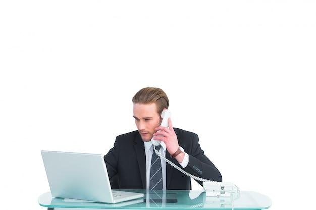 Ernster geschäftsmann, der laptop beim anrufen verwendet