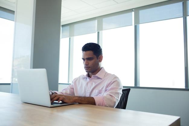 Ernster geschäftsmann, der laptop im konferenzraum benutzt