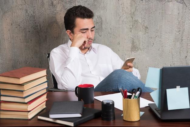 Ernster geschäftsmann, der mit telefon am schreibtisch spielt.
