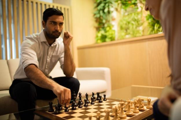 Ernster geschäftsmann, der schach mit kollegin spielt
