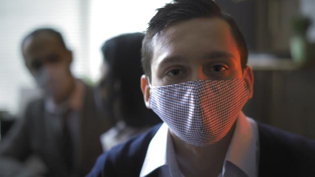 Ernster geschäftsmann in der schutzmaske, die von rotem neon hinterleuchtet wird