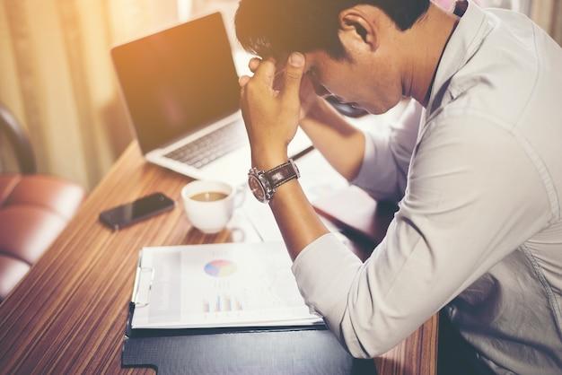 Ernster geschäftsmann mit analyse finanz im büro arbeiten.