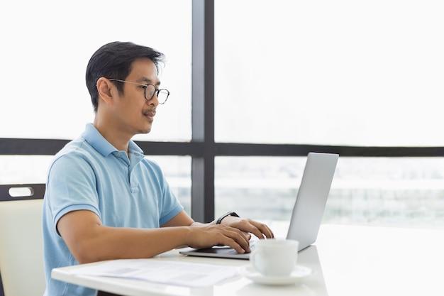 Ernster geschäftsmann mit brille, der zu hause am laptop tippt