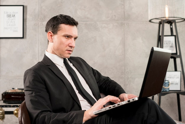 Ernster geschäftsmann mit dem laptop, der zu hause arbeitet
