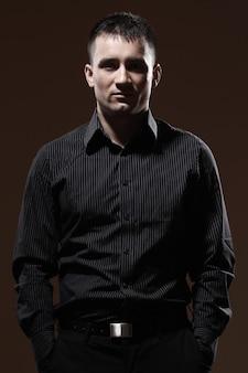 Ernster geschäftsmann mit gestreiftem schwarzem t-shirt und schwarzer hose