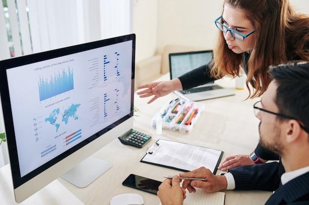 Ernster geschäftsmann und geschäftsfrau, die diagramme und diagramme mit statistiken auf computerbildschirm diskutieren