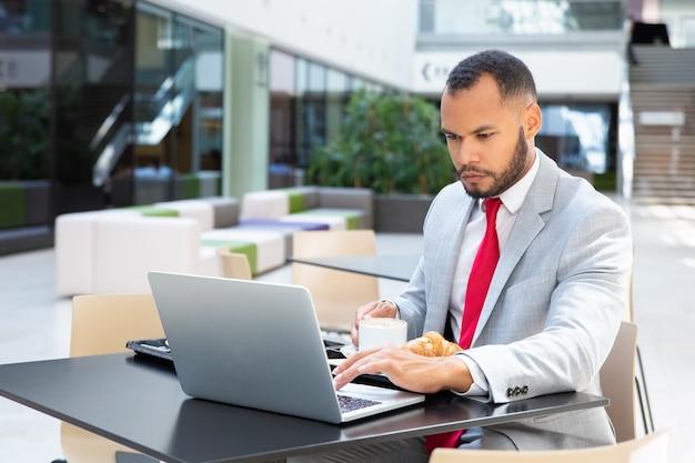 Ernster geschäftsmann unter verwendung des laptops im café