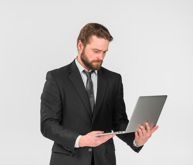Ernster geschäftsmann unter verwendung des laptops