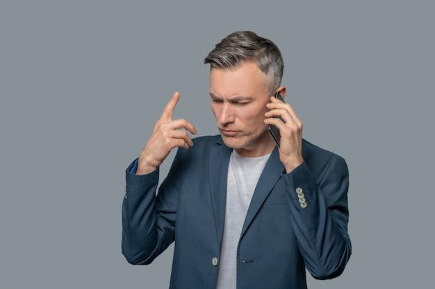 Ernster gestikulierender mann, der auf smartphone spricht