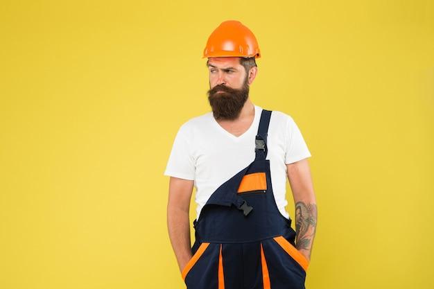 Ernster gipser. mann baumeister in schutzhelm. zur sicherheit einen helm tragen. experte für bauen. brutaler arbeiter mit bart. er ist nur ein handwerker. wähle deinen beruf. bauingenieur in arbeitsuniform.