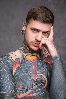 Ernster hemdloser junger mann mit tätowierung auf seiner karosserie, die kamera betrachtet