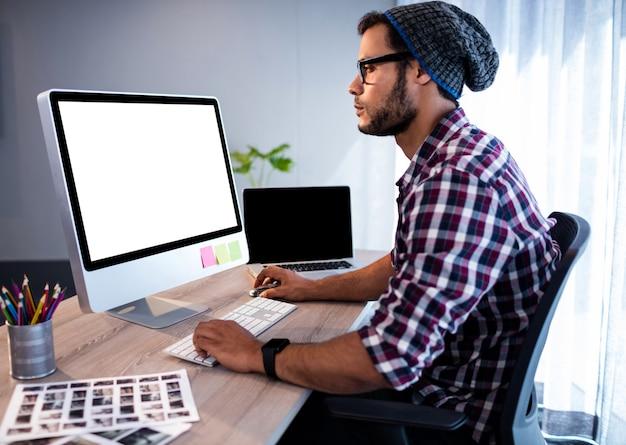 Ernster hippie, der am computertisch arbeitet