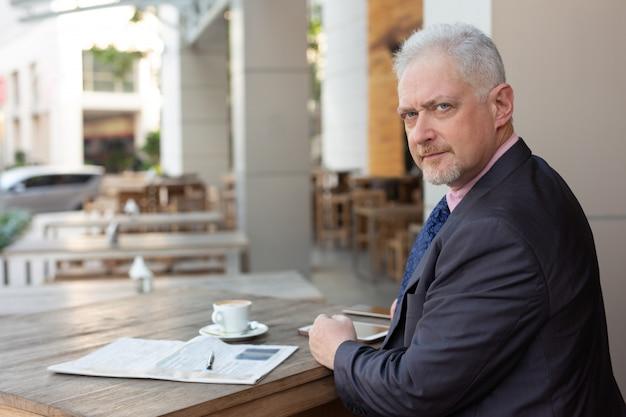 Ernster hübscher geschäftsmann in der klage, die im straßencafé arbeitet