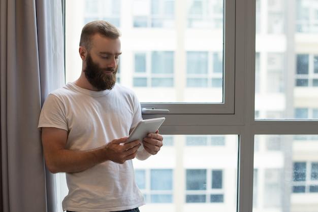 Ernster hübscher hippie-kerl, der zu hause digitale tablette verwendet